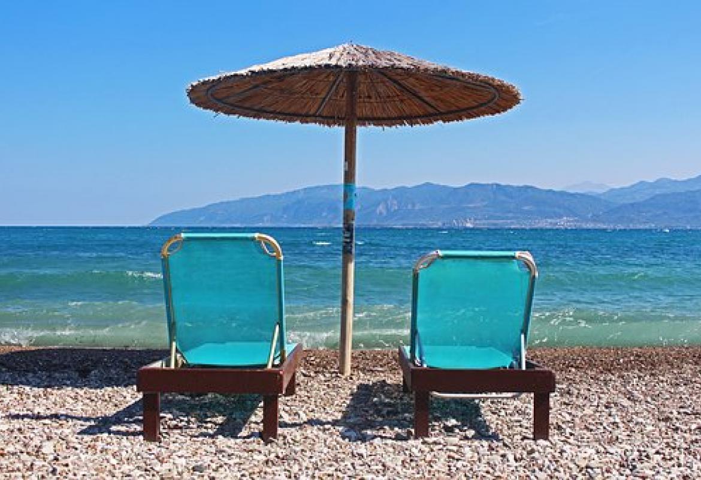 Sombrilla con dos sillas debajo en una playa