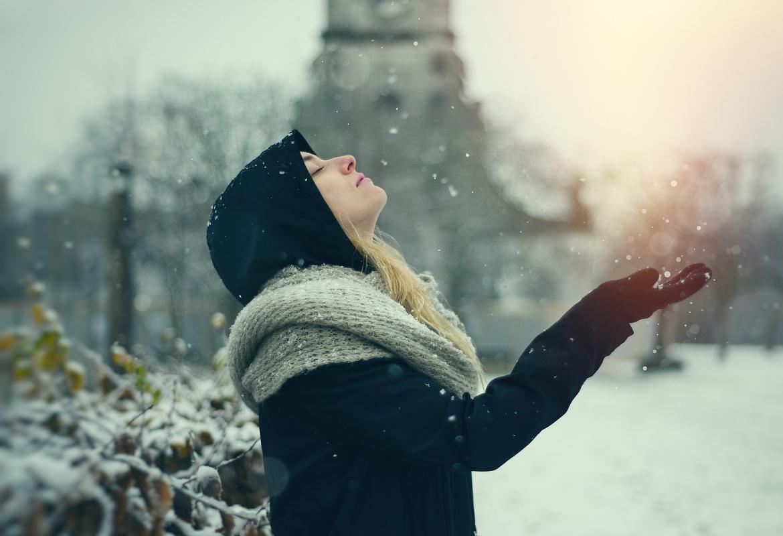 chica bajo la nieve observando los copos