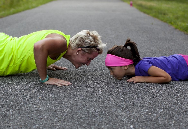 Chica y niña en el suelo haciendo flexion