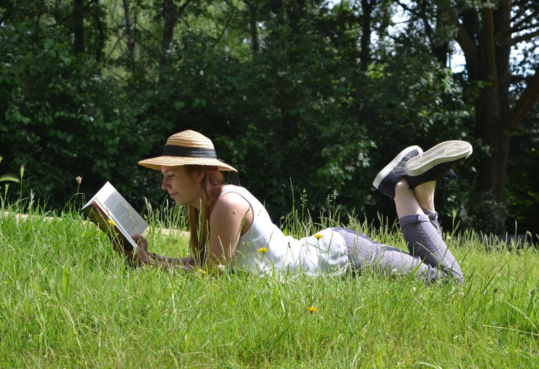 chica tumbada en la hierba leyendo