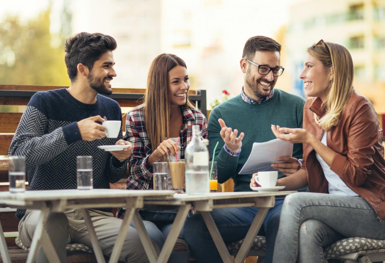 cuatro chicas y chicos jóvenes sentados tomando café sonrientes