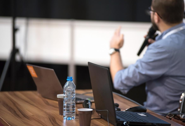 hombre trabajando hablando por teléfono y botella con ordenador sobre la mesa