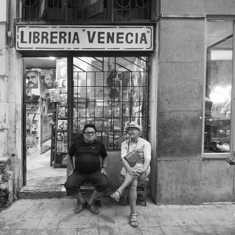 Dos hombres sentados a la puerta de un comercio