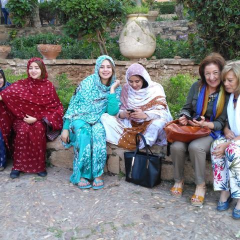 Dos mujeres mayores sentadas junto a jóvenes con hiyab