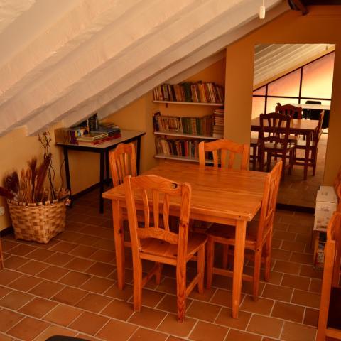 Habitación abuardillada con mesa sillas y ordenador albergue juvenil Las Dehesas